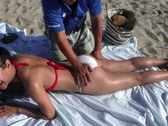 Guy Doing A Massage On A Girl On The Beach In A Bikini