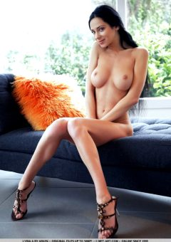 Busty Lydia A poses naked on the couch
